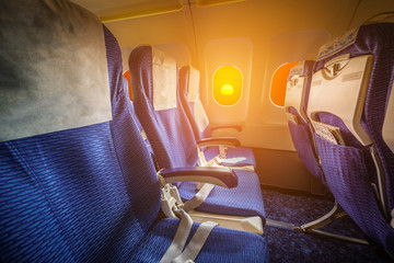 Empty seats interior of an airplane at sunset.