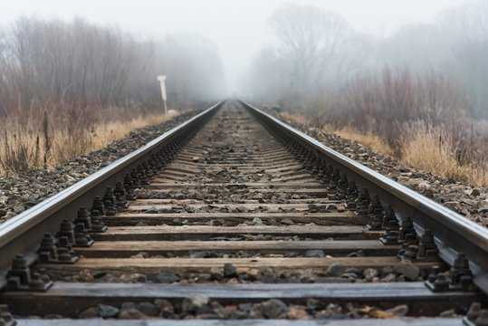 Empty railroad track going into a fog, outdoor landscape