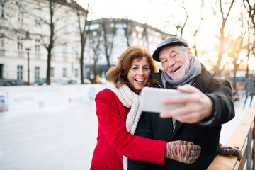 Senior couple with smartphone on a walk in a city in winter.
