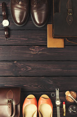 Top view, fashionable male and female personal items with space on a dark wooden background. Leather bag, shoes, watches, stylish accessories.