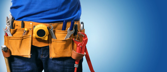 closeup of handyman tool belt on blue background with copy space
