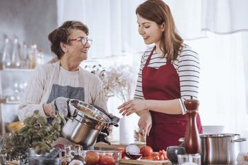 Grandma and granddaughter cooking soup