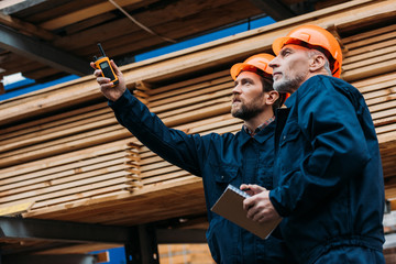builders in helmets pointing with walkie talkie on construction
