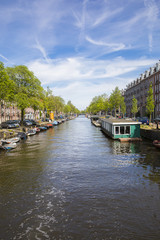 Amsterdam, the Netherlands - 23 May 2017: perspective view on canal Lennepkade boarded with boats and house boats and brick buildings