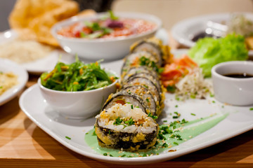 Healthy vegan table - a roll of sushi, wakame algae salad, chickpeas in tomatoes and falafel