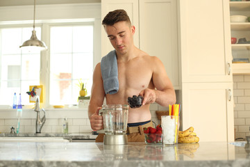 Young man with no shirt on making a healthy smoothie.
