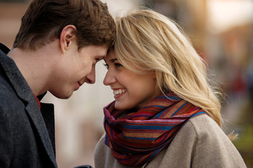 Waist up portrait of lovely playful couple looking right into eyes expressing curiosity and happiness