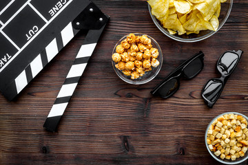 Crisp, popcorn, rusks for watching film. Clapperboard and glasses on dark wooden background top view copyspace