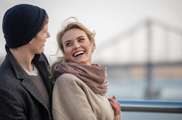 True emotions. Waist up portrait of lovely man and woman looking at each other while standing in open air near river with bridge on background. Copy space in right side