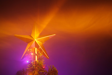 Christmas tree shiny star, purple background with smoke
