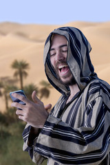 Young Arab, having a fun conversation by mobile phone.