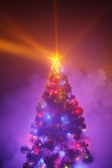 Christmas tree with festive lights, purple background with smoke