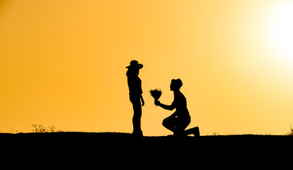 young couple silhouette at sunset