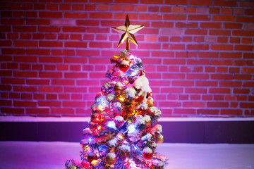 Christmas tree with festive lights in snow outdoors, purple brick wall background