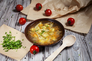 vegetarian soup of fresh greens, vegetables and pasta in a brown plate, chopped green onion on brown baking paper and cherry tomatoes on a light wooden table