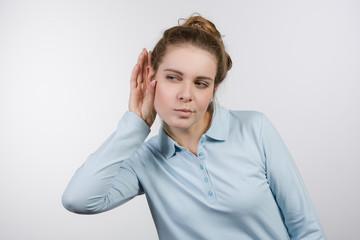Junge Frau hält sich die Hand ans Ohr und lauscht