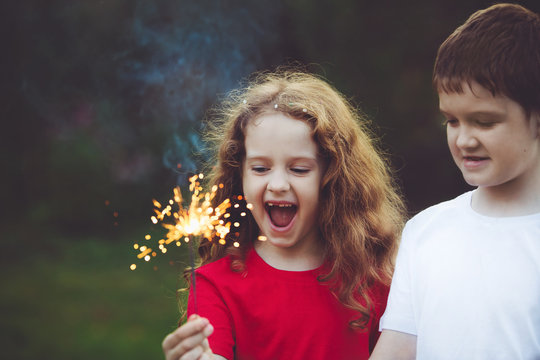 Happy friend child in party with burning sparkler in his hand.