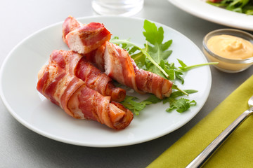 Plate with bacon wrapped chicken nuggets on table