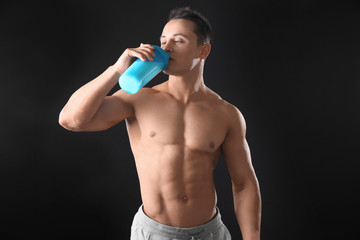 Sporty young man drinking protein shake on black background