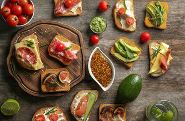 Delicious sandwiches on wooden background, top view