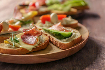 Wooden plate with delicious sandwiches on table, closeup