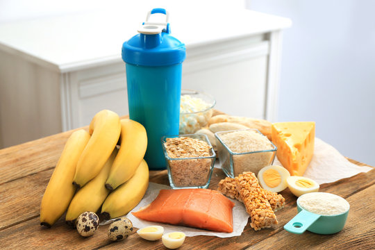 Scoop with protein powder, shake in bottle and products on table