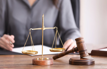 Scales of justice and judge hammer on table in notary's office