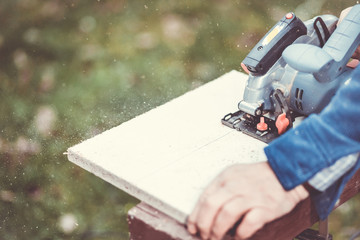 Man cutting huge piece of wood by electric circular saw (color toned image)