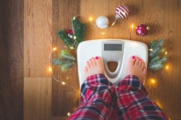 Top view of female feet in winter pajamas on digital scales or weight scale on wooden background surrounded with Christmas lights and decoration. Weight gain during holidays concept, vintage toned