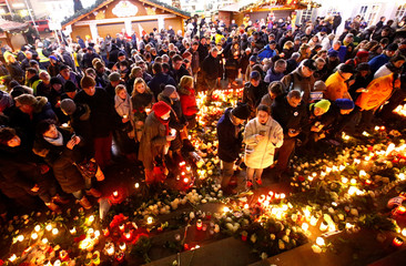 People hold candles at the memorial at the site of last year's truck attack in a Christmas market, which killed 12 people and injured many others, at Breitscheidplatz square in Berlin