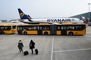 People disembark a Ryanair flight to board a bus on the tarmac at Stansted airport in London