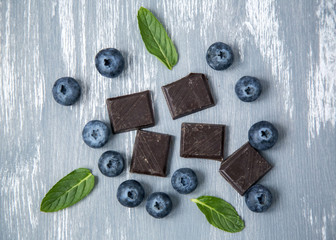 Closeup Dark Chocolate Fresh Organic Blueberries Fresh Mint Leaves Scattered on Wooden Background Natural Light Selective Focus Top View