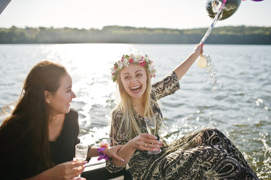 Girls drinking champagne at yacht on hen party.