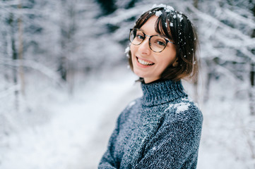 Beautiful positive fashionable stylish modern brunette girl in trendy glasses looking at camera. Cute lovely teenager person with tender kind simple face. Soft focus portrait. Woman with snow on hair.