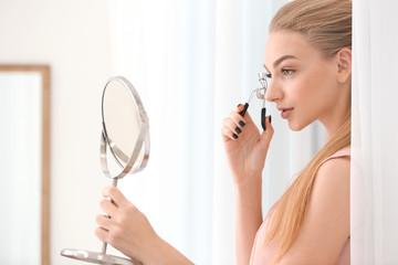 Beautiful young woman using eyelash curler at home