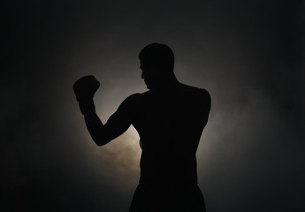 Silhouette of strong male boxer on dark background