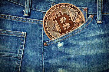 Golden Bitcoin in a jeans pocket. Photo (new virtual money ) New crypto currency in the form of the coins.