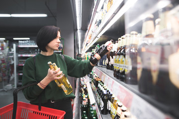 A beautiful girl takes alcoholic drinks from the supermarket shelf. Shopping for alcohol in the store. The girl chooses a drink in the supermarket. Fototapete