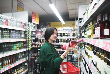A beautiful girl looks at the wine bottle carefully when shopping at the supermarket. The girl reads a wine label. Shopping in a supermarket.
