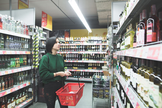 Beautiful young girl chooses wine in a supermarket. The buyer buys alcohol at a supermarket. Look at the supermarket shelf.