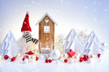 Snowman with Christmas ornaments and toy house and Christmas lights. Festive Christmas background