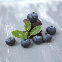 Closeup Dark Chocolate Stack Fresh Organic Blueberries Fresh Mint Leaves on Wooden Background Natural Light Selective Focus