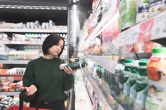 A beautiful girl reads a yogurt label in the supermarket milk department. The girl is shopping at the supermarket.