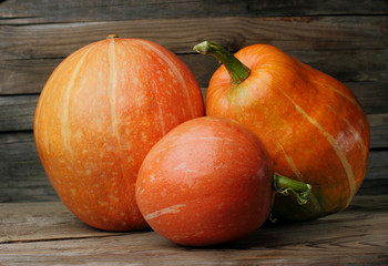Three pumpkins big medium and small on wooden table with bokeh background. The concept family.