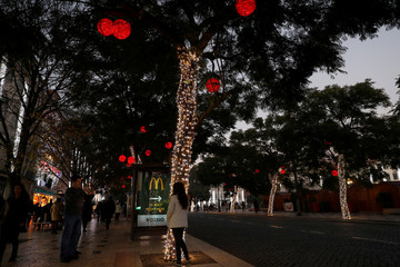 People take pictures with trees decorated with Christmas lights at Rossio square in downtown Lisbon