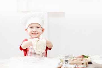 Little child making pizza or pasta dough