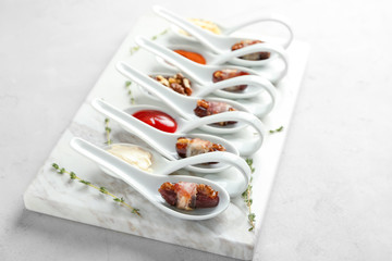 Spoons with bacon wrapped dates on table