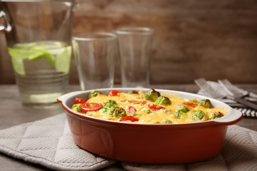 Baking dish with Brussels sprouts and cheese on table