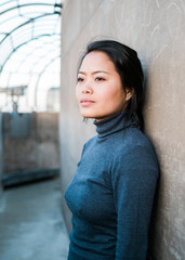 Asian woman in blue shirt looking into the distance