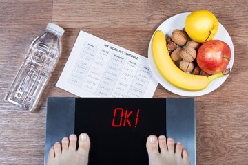 Female feet on digital scales with word ok surrounded by bottle of water, plate with healthy food and workout schedule paper. Concept of active and healthy lifestyle.